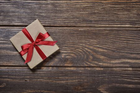 Gift box with red ribbon over wooden background photo