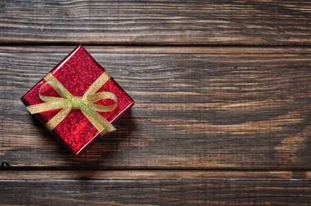 Red gift box with golden ribbon on wooden background photo
