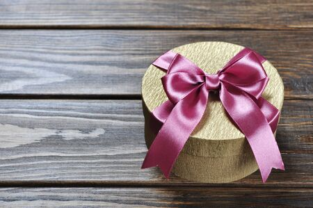 Golden gift box with pink ribbon on wooden background photo