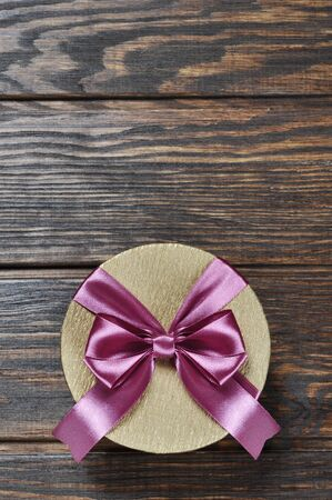 Golden gift box with pink ribbon over wooden background photo