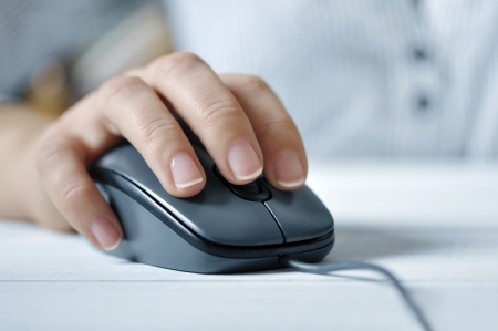 female hand clicking computer mouse closeup. Small shallow DOF. Stock Photo - 17454510
