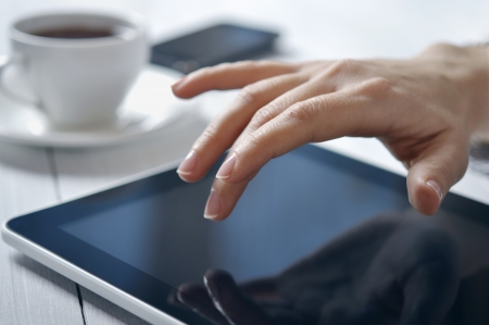 Hands of businesswoman using tablet PC at office photo