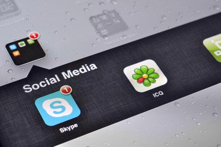 Kiev, Ukraine - Jan 12, 2013: Apple Ipad screen with social media applications of Skype, QIP, ICQ,