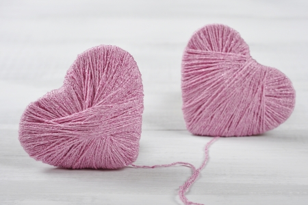 Two pink clews in shape of heart on white wooden background photo