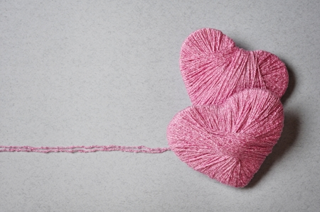 Pink heart shape made from wool on grey background photo