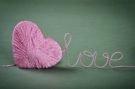 Pink clew in shape of heart with word  'love' made from yarn on green background photo