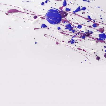 Multi color paint drops on light background closeup photo