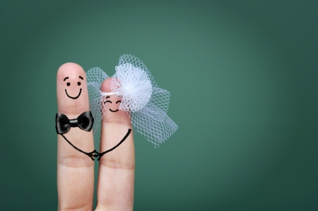 Two happy fingers decorated as bride and groom with veil and bow tie
