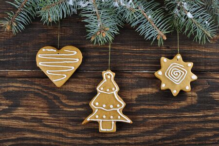 Christmas Ginger and Honey cookies on wooden background with branch of fir tree photo