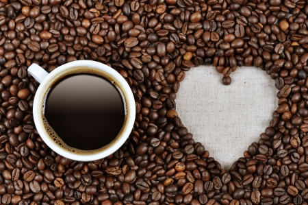 Heart shape made from coffee beans with a cup of coffee on linen fabric. photo