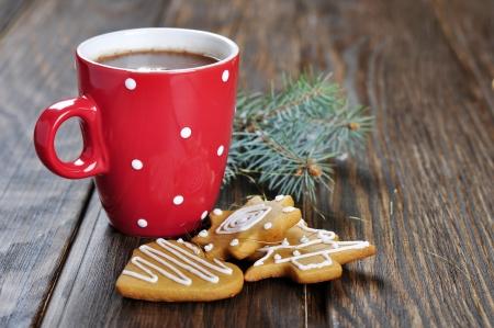 galleta de chocolate: Taza de chocolate caliente, una rama de abeto y galletas de jengibre en un fondo de madera