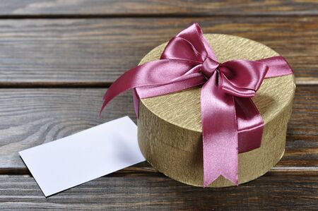 Golden gift box with pink ribbon on wooden background Stock Photo - 17775609
