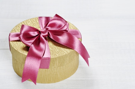 Golden gift box with pink ribbon on white wooden background Stock Photo - 17775574
