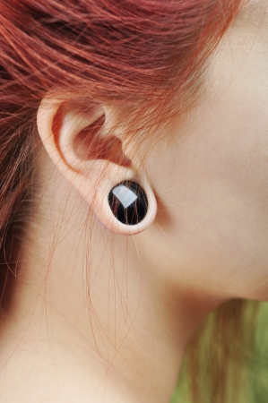 big ear: The big aperture in an ear at the teenager closeup Stock Photo