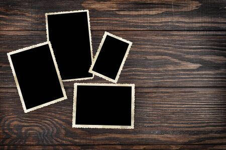 Blank vintage photo frames on old wooden background. Clipping path included. photo