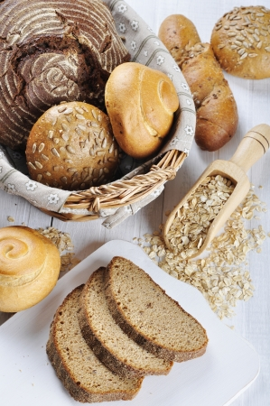 organic flax seed: Composition with bread and rolls in wicker basket over white wooden background