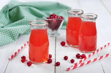 tubules: Cranberry juice in glass jars on a white wooden background