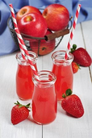 tubules: Strawberry juice in glass jars and fresh apples in vintage basket on a white wooden background