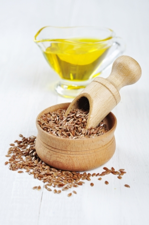 flax seed oil: Wooden Bowl with brown flax seed and linseed oil over white wooden background