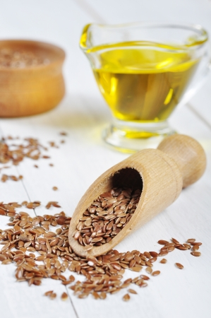 flaxseed: Wooden Bowl with brown flax seed and linseed oil over white wooden background