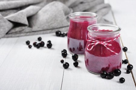 tubules: Cranberry and black currant smoothie in glass jars on a white wooden background Stock Photo