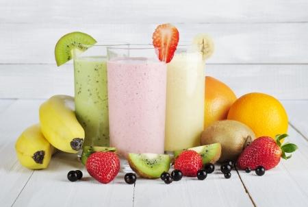 batidos frutas: Batidos de fruta con la grosella negro, fresa, kiwi, naranja y pl�tano en el fondo de madera blanco
