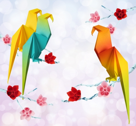 Origami parrots on a branches trees with flowers on green background photo