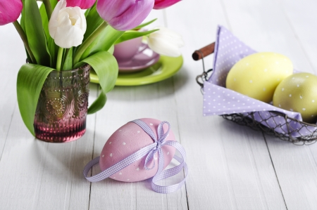 Pink, violet and white tulips in a glass vase with easter eggs on wooden background photo
