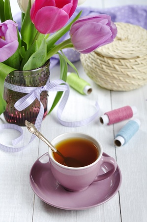 Cup of tea with tulips bouquet in glass vase on white wooden background photo