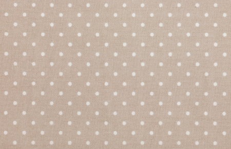 Light brown polka dot fabric closeup. May use as background photo