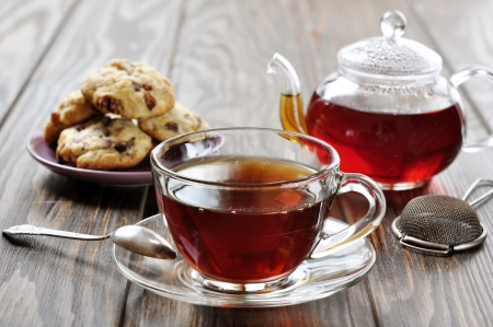 Cup of tea with teapot and cookies on wooden background photo