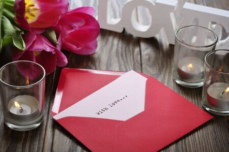 tulips and red open envelope with candles on wooden background photo