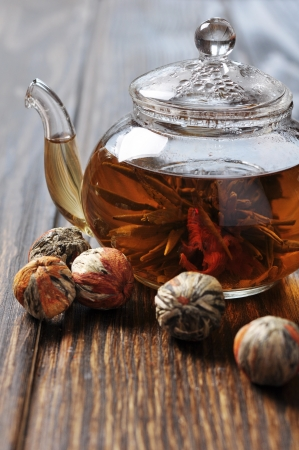 bolls: Chineas flowering tea in glass teapot on wooden background