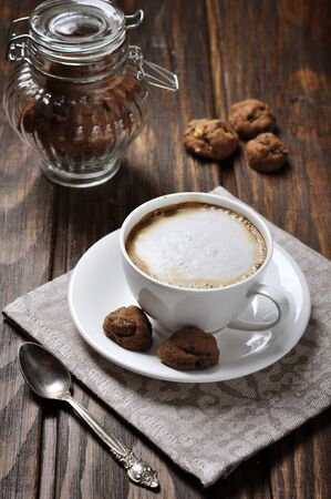 breackfast: Cup of coffee with cookies over wooden background
