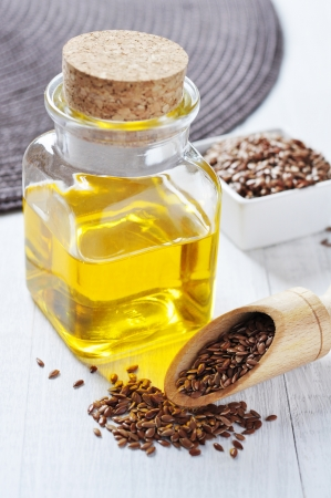 Linseed oil in a glass bottle and flax seeds on a wooden background photo
