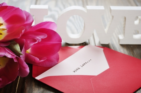 tulips and red open envelope  on wooden background photo