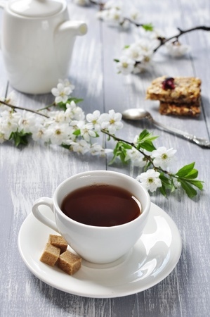 Cup of tea and teapot with branches of blooming cherry on wooden background photo