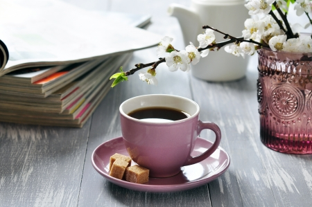 Cup of coffee  with branches of blooming cherry on wooden background photo