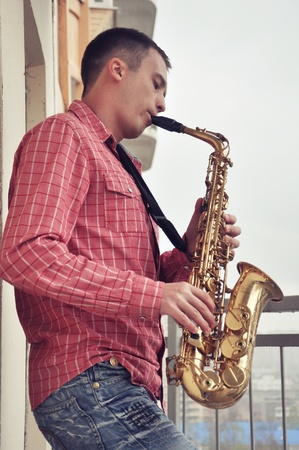 handsome young man playing on saxophone outdoor photo