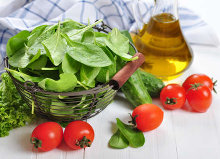tomatos: Fresh spinach leaves in  basket with tomatos, cucumber and olive oil on a white wooden background