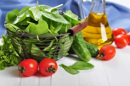Fresh spinach leaves in basket with tomatoes, cucumber and olive oil on a white wooden background photo