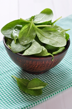 Fresh spinach leaves in brown bowl on a white wooden background photo
