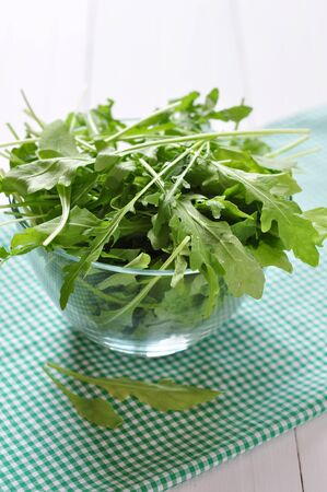 rukola: Fresh arugula leaves in glass bowl on a white wooden background Stock Photo