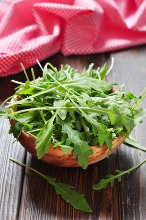 rukola: Fresh arugula leaves in wooden bowl on a wooden background Stock Photo