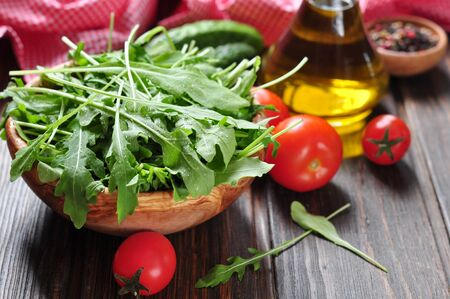 Fresh arugula leaves in wooden bowl with tomatoes, cucumber and olive oil on a wooden background photo