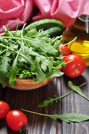 rukola: Fresh arugula leaves in wooden bowl with tomatoes, cucumber and olive oil on a wooden background