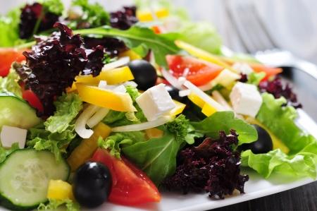 ensalada verde: Ensalada griega en plato blanco sobre fondo de madera de cerca