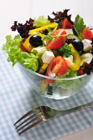 Greek salad in glass bowl on wooden background closeup photo