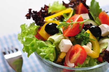 ensalada verde: Ensalada griega en un taz�n de vidrio, de madera, cerca de fondo