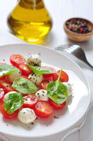 Caprese Salad on white plate with olive oil on wooden background photo